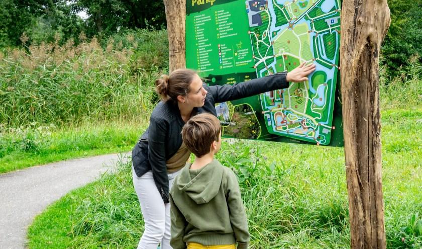Marieke Weishaupt van het Milieu Educatief Centrum bekijkt het nieuwe informatiebord samen met Sebastiaan Bakx die wethouder Binnendijk een handje hielp met de onthulling.