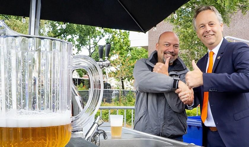 Wethouder Willem Joosten van duurzaamheid (rechts) heeft net de eerste een eco-pitcher bier getapt en schudt de hand van Nico de Bruin van Grand Café Hofplein, die het experiment met de ecoglazen coördineert.