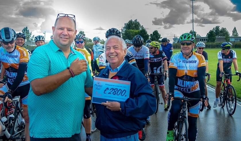 Paco Busteros León (links) overhandigt de cheque met de opbrengst over 2018 aan een vertegenwoordiger van het Instituut Asbestslachtoffers. Op de achtergrond staan de deelnemers aan de toertocht klaar voor de start.