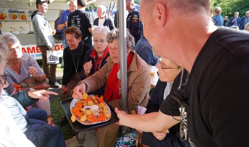 Bestuurslid Christ Kreugel van de Vrienden van het Oude Dorp trakteert de vrijwilligers op lekkere snacks.