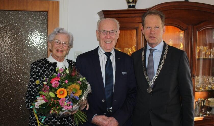 Het stralende paar met burgemeester Arie van Erk. | Foto: Annemiek Cornelissen.