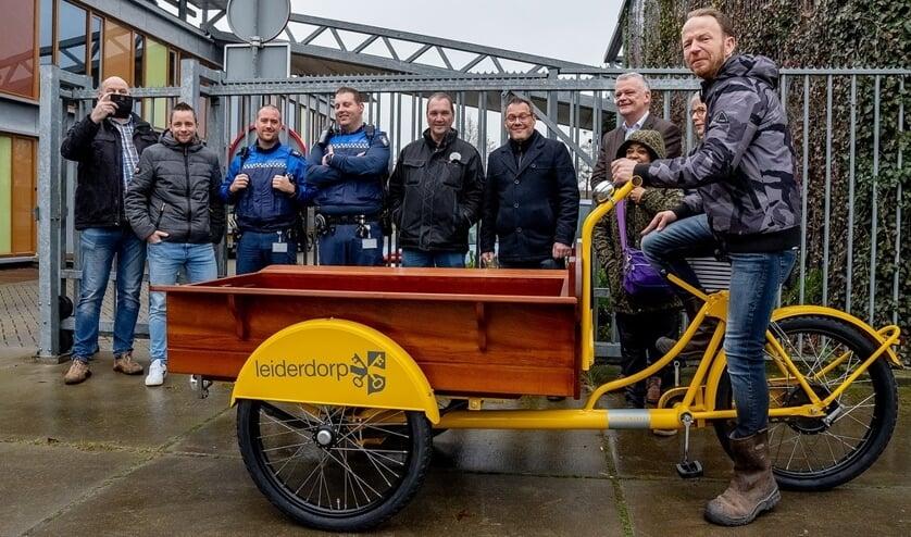 Ron Sanders op zijn gloednieuwe bakfiets met achter de fiets wethouder Daan Binnendijk en Ron's supporters.