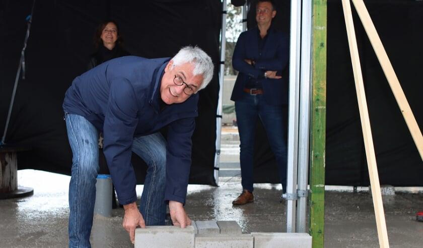 <p>Symbolisch tilt de wethouder de eerst steen op zijn plek. | Foto: gemeente Noordwijk</p>