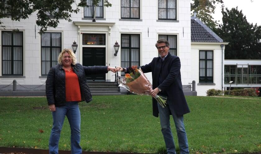 Marieke Noordermeer krijgt van Willem Heemskerk als afscheid een boks en een bloemetje.