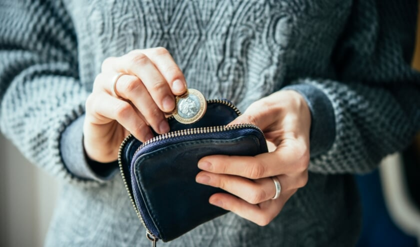 <p>Hands holding british pound coin and small money pouch</p>