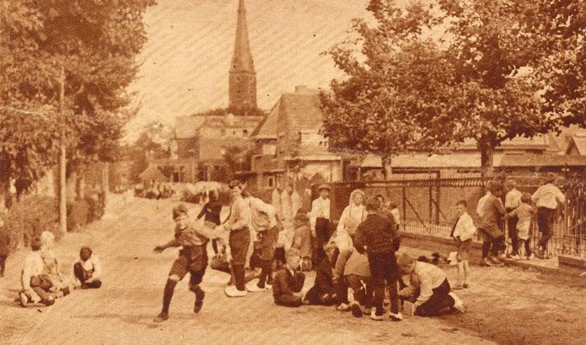 De Herenstraat met spelende kinderen voor de katholieke jongensschool omstreeks 1929.