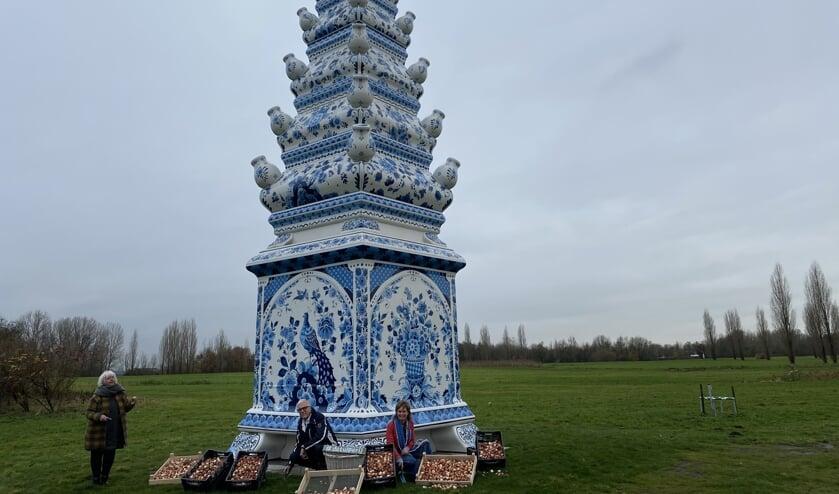 <p>Paula Kouwenhoven, Henk Schouten en Anja Jansze poten de eerste tulpenbollen bij de Delfts Blauwe Tulpenpiramide langs de A13.&nbsp;&nbsp;</p>