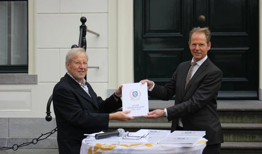 <p>Koos van der Klugt overhandigt de burgemeester &#39;Honderd jaar voetbal in Hillegom&#39;. | Foto: Annemiek Cornelissen.</p>