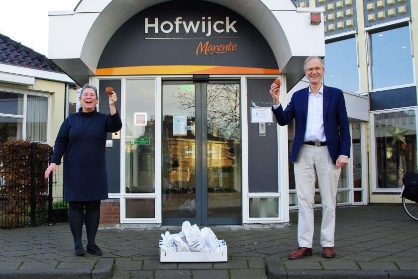 <p>Locatiemanager Renate Claassen van Hofwijck nam blij de oliebollen in ontvangst van wethouder Jan Nieuwenhuis.   Foto Willemien Timmers</p>