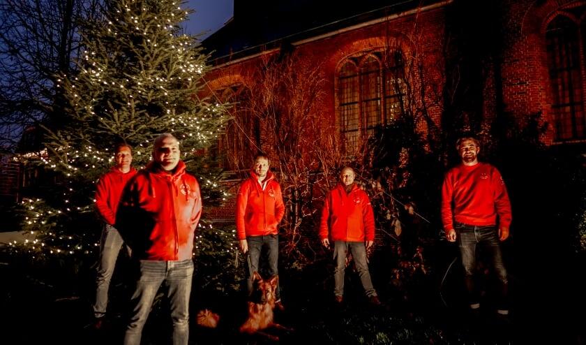 <p>Voorzitter Herbert Zilverentant (linksvooraan) en vier bestuursleden van de Vrienden van het Oude Dorp bij de verlichte kerstboom.&nbsp;</p>