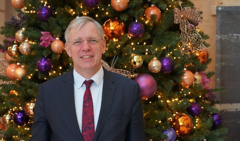 <p>Burgemeester Visser voor de Kerstboom in het stille gemeentehuis. | Foto: Marc Wonnink</p>