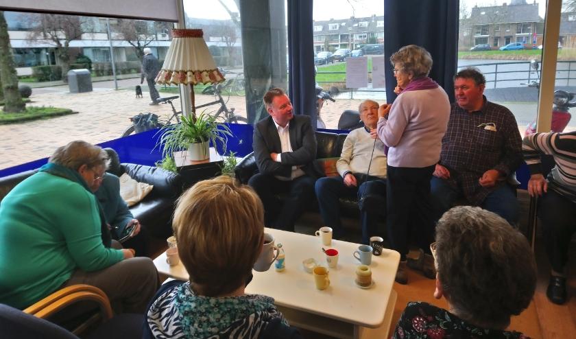 Rik van Woudenberg (geheel links op de bank) in gesprek met de bezoekers van 't Buurthuis.
