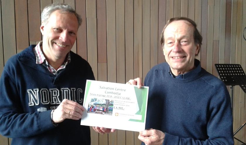 Werelddiakenen Jan van der Wel en Cor van Viegen lieten twee weken geleden, toen het ernaar uit ging zien dat de overhandiging in de Dorpskerk niet door kon gaan, de cheque zien.