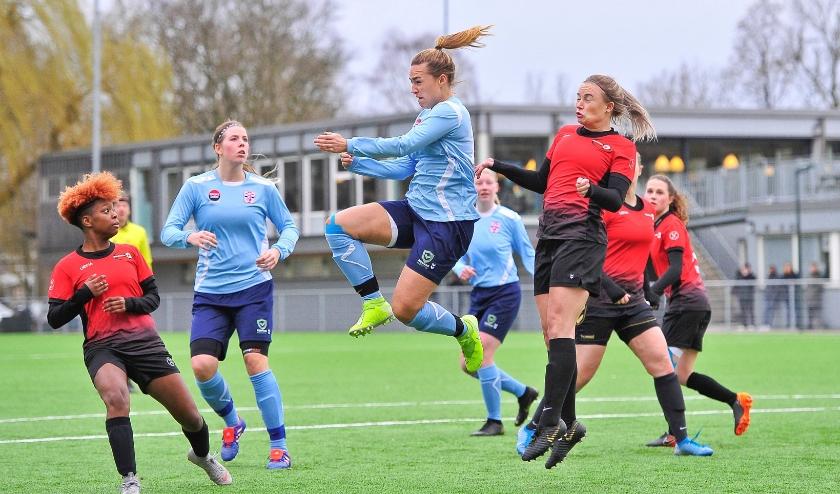 Yara Haasnoot klimt hoog in de lucht en kopt de bal door.
