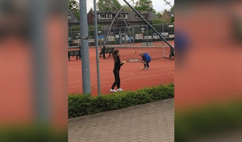 Lisa Schouten op de tennisbaan. De foto is gemaakt door haar moeder die door het hek van een afstandje mocht toekijken.