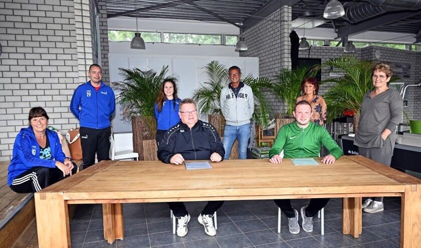 De nieuwe trainers Rob Berreboom (links aan tafel) en Dennis van der Horst (rechts) bij de contractondertekening.