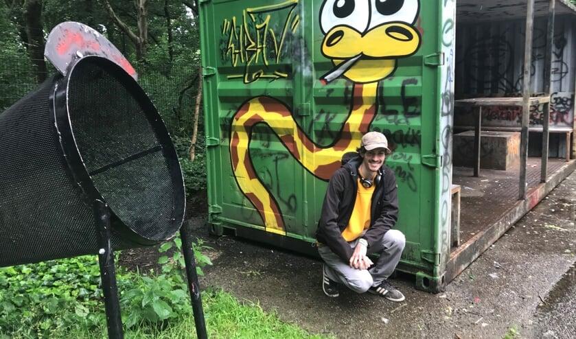 Dennis Bonsen, in de graffiti scène ook bekend als Girav, poseert bij zijn kunstwerk in de Bloemerd.