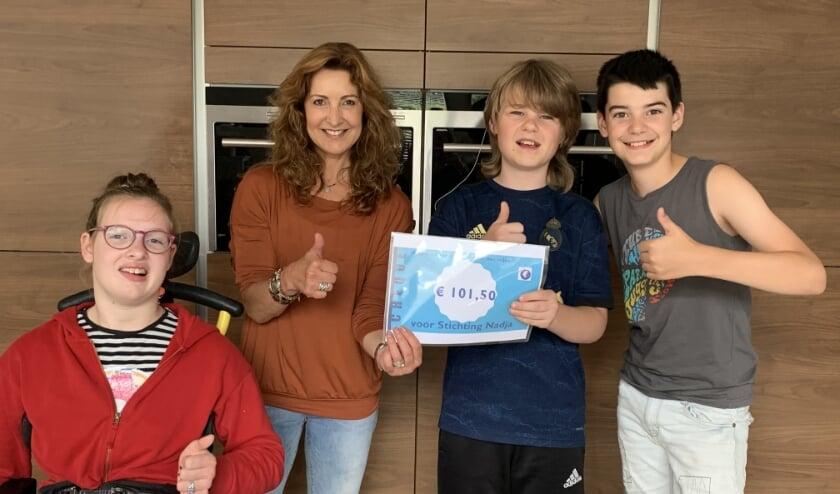 Dani en Jasper (rechts) reiken de cheque uit aan Nadja en Anne  van Stichting Nadja.