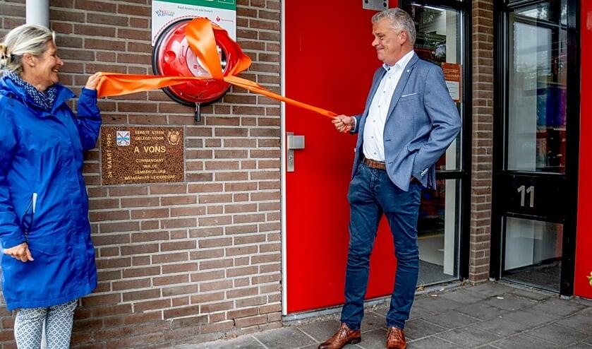 Voorzitter Divera Kapteijn van de EHBO-vereniging Leiderdorp en wethouder Daan Binnendijk openen de nieuwe AED bij de brandweerkazerne.