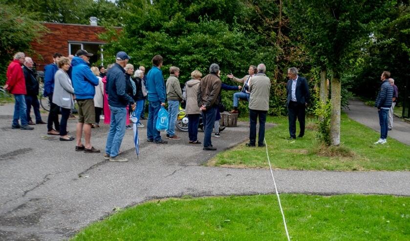 Joosten (5e van rechts) praat met bewoners. Het touw op de grond laat zien hoe breed een doorfietspad zou worden.