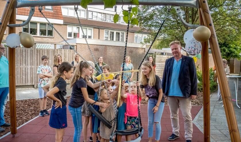 Wethouder Rik van Woudenberg kijkt toe hoe kinderen uit de buurt hun speeltuin openen.
