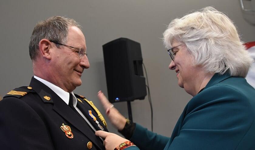 Erik van der Veld krijgt zijn onderscheiding opgespeld door zijn echtgenote. | Foto: Piet van Kampen