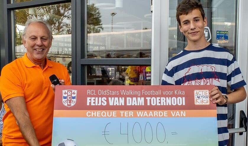 Feijs van Dam overhandigt de toernooiopbrengst aan een vertegenwoordiger van KiKa.