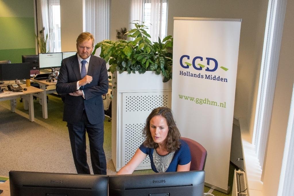 De Koning in gesprek met de coördinator bron- en contactonderzoek.  Foto: GGD HM Ed Hölscher © uitgeverij Verhagen