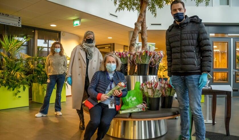 Linda Bezuijen (met beige jas) en Sjoerd Verbree van Vegro overhandigden de tulpen aan medewerkers van De Ommedijk. | Foto: J.P. Kranenburg