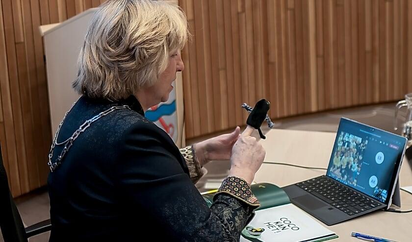 <p>Burgemeester Driessen, met Coco-vingerpoppetje, achter haar laptop waarop ze haar jonge publiek ziet.</p>