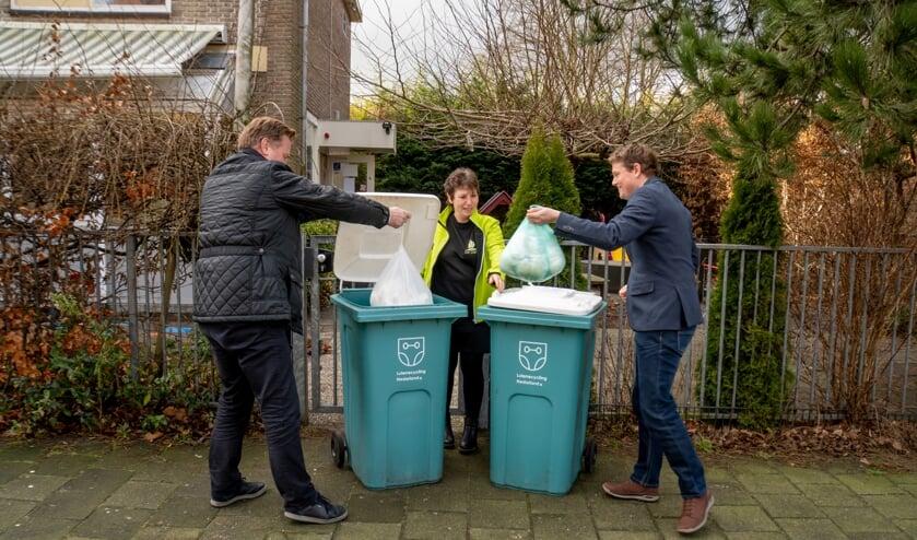 <p>Wethouder Rik van Woudenberg (links) en GroenLInks fractievoorzitter Bob Vastenhoud gooien onder toeziend oog van Petra Kappetein van De Dartel zakken met luiers in de inzamelbakken.&nbsp;</p>