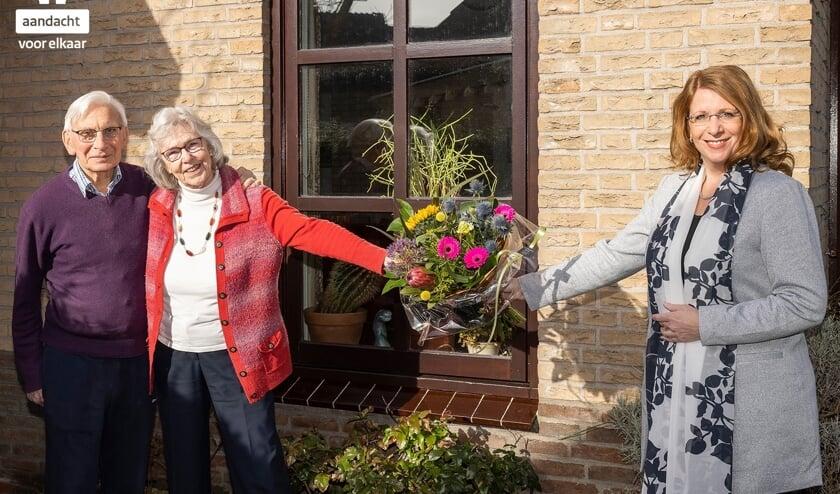 <p>Burgemeester Breuer overhandigt een bloemetje aan het echtpaar Schouten.</p>