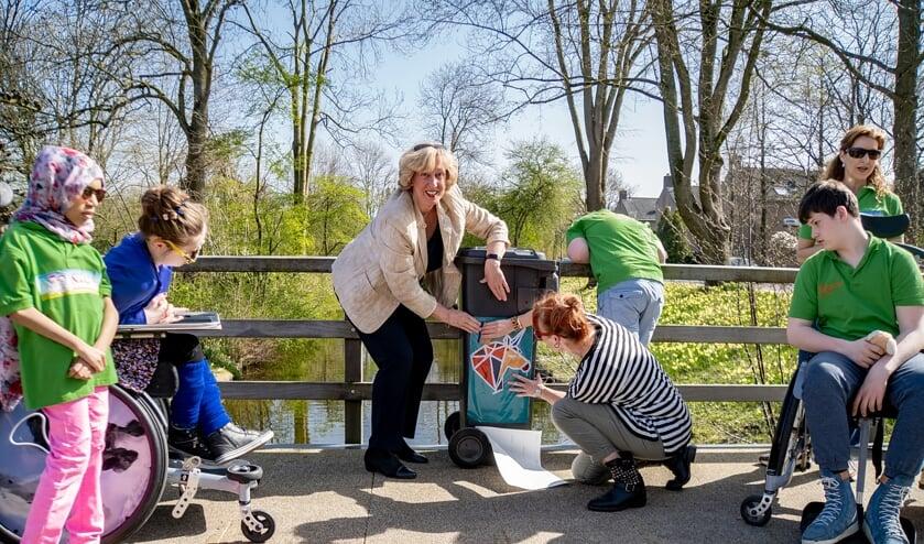 <p>Burgemeester Driessen en Elke van Geest beplakken een afvalcontainer met een van de fraaie stickers. Nafiso, Nadja, Wesley en Anne kijken toe.</p>