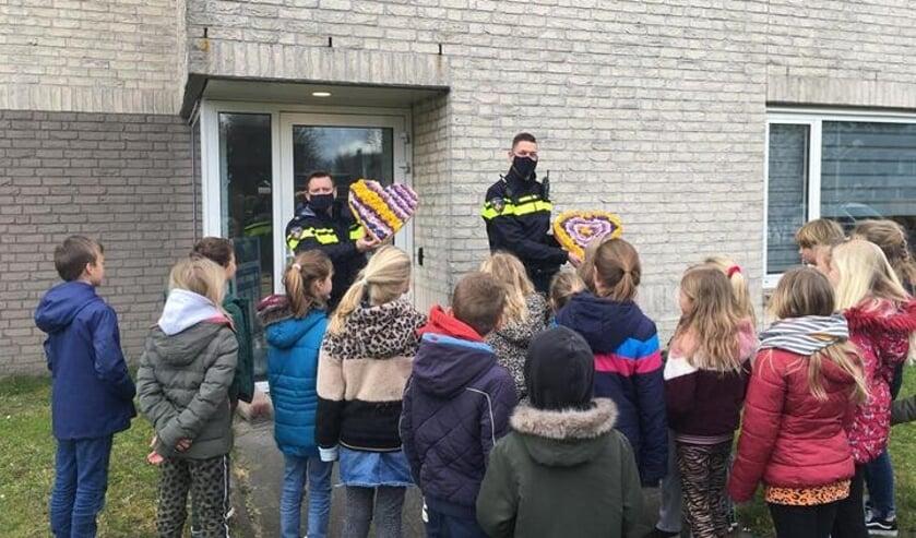 De wijkagenten krijgen een corsohart cadeau van leerlingen van de Overplaats.