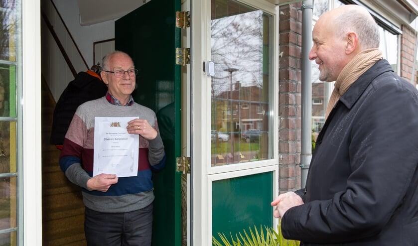 <p>Wim Prins ontvangt aan de deur de Zilveren Barensteel van wethouder Arno van Kempen.&nbsp;</p>
