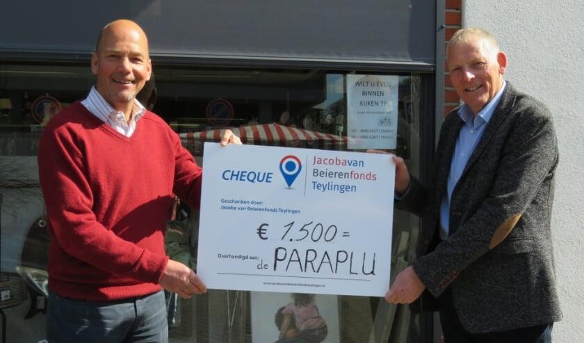 <p>Marcel van den Broek (Jacoba van Beierenfonds) overhandigt een cheque Piet Overduin (voorzitter van de Paraplu). | Foto: pr.&nbsp;&nbsp;</p>