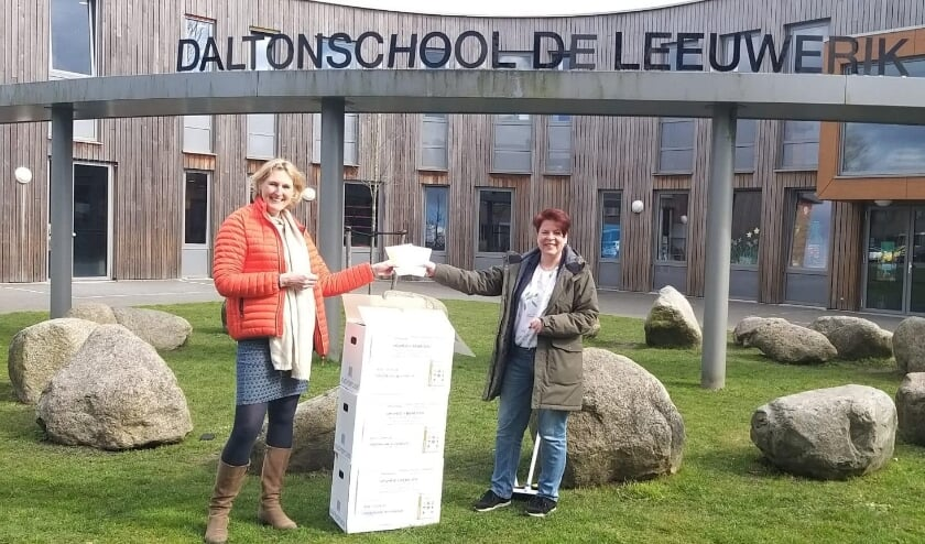Esther Baars (links) van de Oranjevereniging Leiderdorp overhandigde de Vrijheidsboxen aan Marian Soullié van basisschool De Leeuwerik.