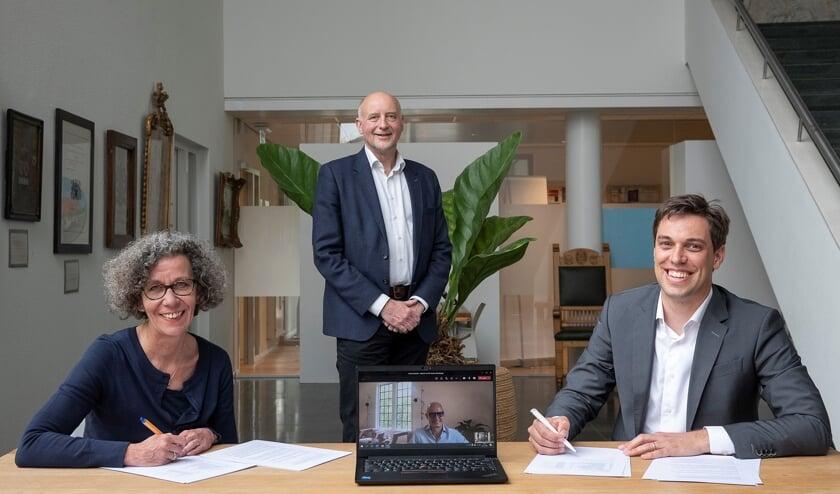 <p>Wethouders Marlies Volten en Arno van Kempen (staand) ondertekenen de overeenkomst met ontwikkelmanager Stefan van Vliet (rechts). Ontwikkelaar Ewoud Swaak is digitaal aanwezig. | Foto: pr.</p>