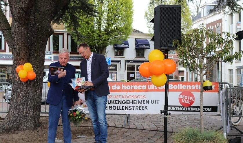 Harry Mens krijgt het eerste exemplaar uit handen van Rotary-lid Kees Hogervorst.