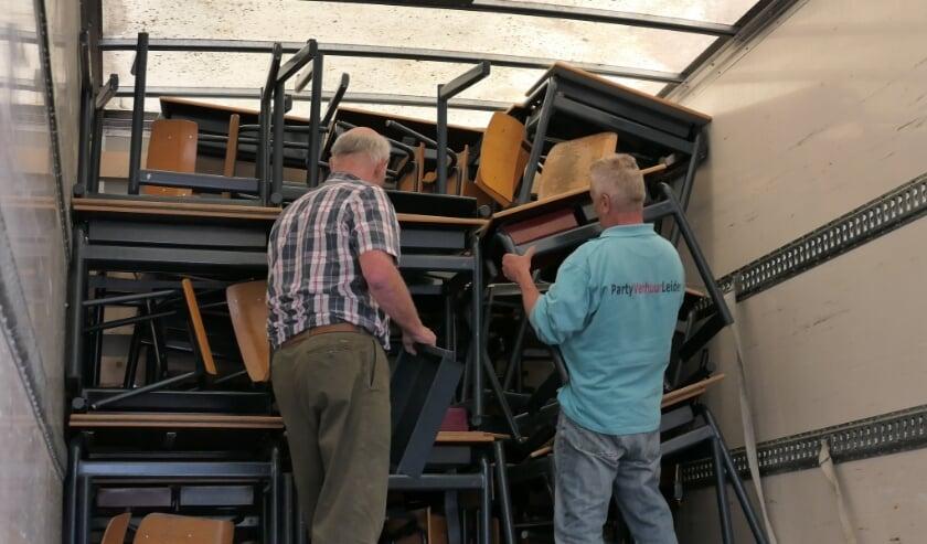 <p>Passen en meten om het schoolmeubilair in de vrachtwagen te krijgen. | Foto: Aart Broek</p>