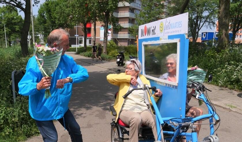 <p>Fietsmaatjes voorzitter Ben Crul overhandigt de bloemen aan Pieta Liefers, vrijwilliger Elly Meijer kijkt toe. | Foto: Carla Kramer</p>